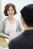 男性と会話をする仕事中の20代女性