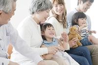 ソファに座り団らんする日本人三世代家族