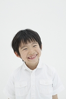 白バックに立ち微笑む小学生