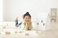 リビングで寛ぐ日本人の女の子と木の家