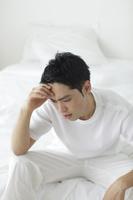 寝起きから体調のすぐれない日本人男性