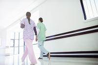 病院の廊下を歩く看護師の後ろ姿