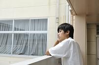 外を眺める男子高校生