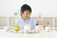 貯金箱にお金を入れる日本人の男の子