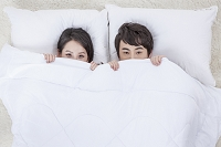 布団をかぶる若いカップル