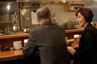 居酒屋で話をするビジネスマンとビジネスウーマン