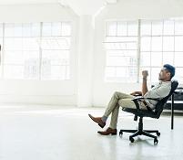 オフィスで椅子に腰かけるビジネスマン