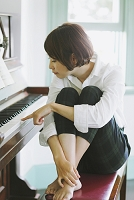 ピアノの鍵盤を叩く女性