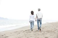 砂浜を歩く中年夫婦の後姿