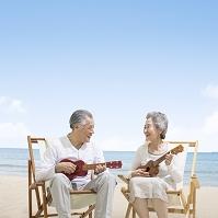 海辺でウクレレを弾くシニア夫婦