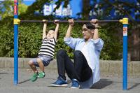 鉄棒で遊ぶ日本人親子