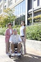 車椅子のシニア男性とシニア女性と女性介護士