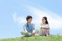 芝生に座る男女