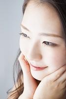 頬に触れて微笑む日本人女性