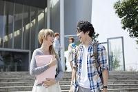 校舎の前で話をする笑顔の留学生と大学生