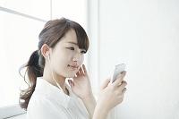 携帯で音楽を聴く女子大生