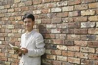 レンガの壁の前で本を持って立つ中年男性