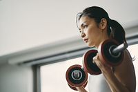 ダンベルトレーニングをする日本人女性