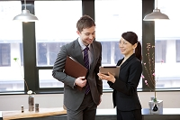 タブレットを見て話すグローバル企業の日本人ビジネスパーソン