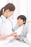 病室で話をする男の子と看護師