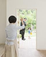 手を振って家族を見送る母親