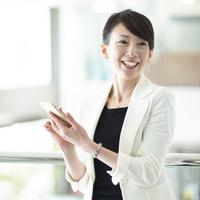 スマートフォンを持ち微笑む日本人ビジネスウーマン