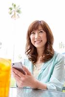スマートフォンを操作している笑顔の日本人女性