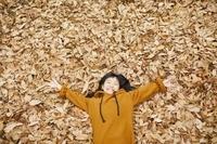 落ち葉で遊ぶ日本人の子供