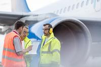 書類をチェックする飛行機の整備士