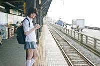 駅のホームでスマートフォンをさわる女子高生