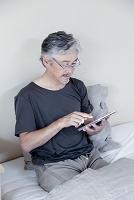 ベッドでタブレットを触るミドル男性