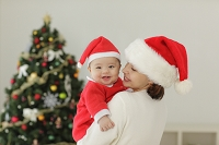 赤ちゃんサンタを抱くママとクリスマスツリー