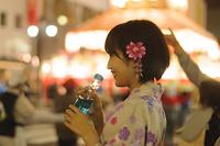 ラムネを飲む浴衣姿の若い女性