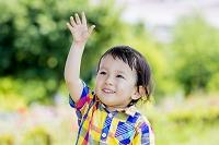公園で手を上げる日本人の男の子