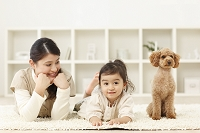 リビングで並ぶ女の子とお母さんとトイプードル