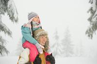雪の中で肩車をする親子