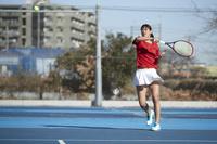 ボールを打つ女子テニス選手
