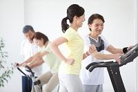 ランニングマシンで運動する日本人女性と男性