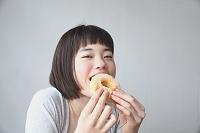 ドーナツを食べる若い日本人女性