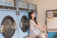 洗濯が終わるのを待っている女性