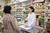客に薬の説明をする日本人女性薬剤師