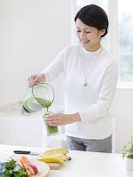 コップに野菜ジュースを入れる女性