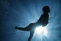 海を泳ぐ女性のシルエット
