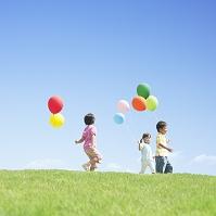風船を持って歩く日本人の子供達