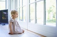窓から遠くを見る子供