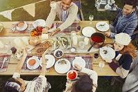 庭で友人と食事をする若者