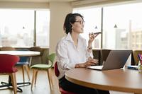 シェアオフィスでスマホでスピーカー通話する女性