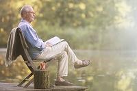 湖畔で読書をするシニア男性