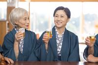 ビールで乾杯す浴衣と羽織の母と娘