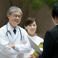 製薬会社の営業マンと話を聞く医者と看護師